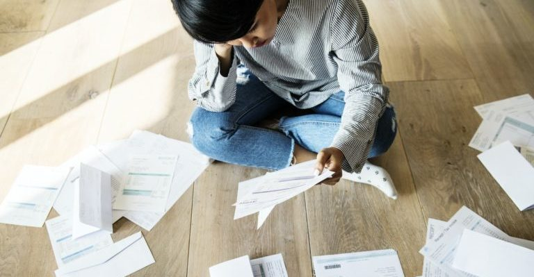 person sitting on the floor reviewing her finances