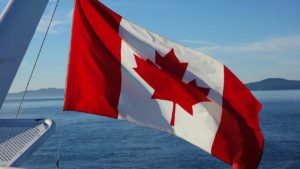 Canadian flag flying over the ocean from the side of a boat