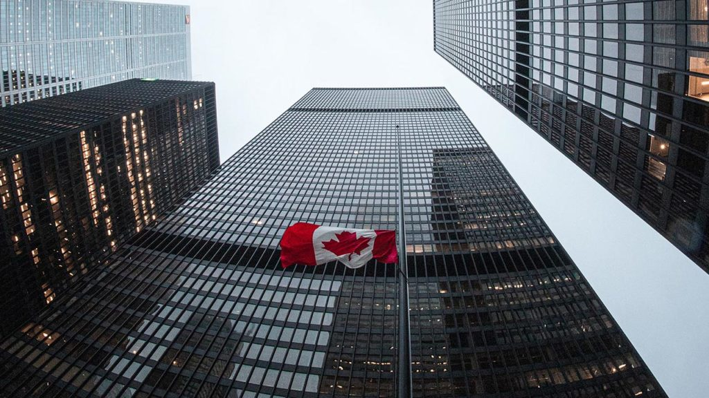 a view from the street of tall buildings and a Canadian flag
